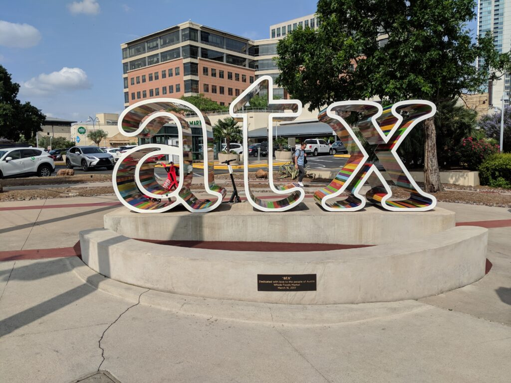 ATX sign and dedication plaque erected in 2017 at West 5th & North Lamar by the original Whole Foods Market located in Austin